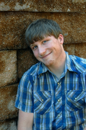 short sleeved: Young man, wearing a blue plaid short sleeved shirt, leans against a stone wall.  He has an amused expression on his face.