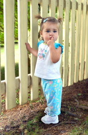 Baby girl struggles with the decision to let go as she learns to walk with the aid of the backyard picket fence.  She has her finger in her mouth and looks quite puzzled. photo