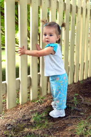 Toddler clings to something solid; a wooden picket fence.  She is stepping a slat at a time.  Her hair is in pig tails and her pants are a blue print.