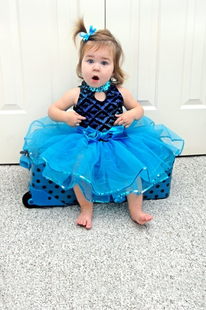 coordinating: Little girl dressed as a ballerina is astounded to realize she could actually become one someday.  She is ready for the road show with coordinating suitcase with black polka dots.