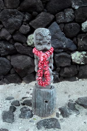Ancient tiki stands guard at the beach of Puuhonua o Honaunau National Historical Park on the Big Island of Hawaii.  A lei of pink plumeria has been left as a gift. photo