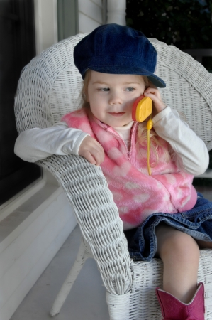 little girl holds play cell phone to her ear as she sits on her front porch.  She is wearing a denim skirt, cap and bright pink boots. Stock Photo - 15044699