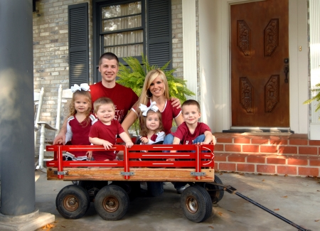 Family of six smile for a family photo.  They are all dressed in red and sitting on the front porch of their home.  Four kids are sitting in a red wooden wagon. Stock Photo