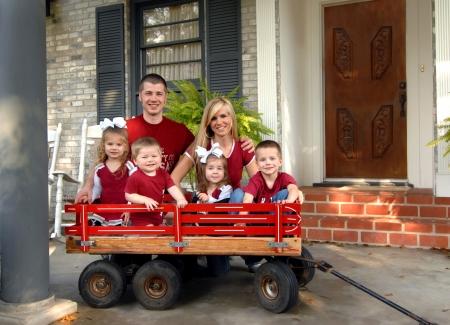 Gezin van zes glimlach voor een familiefoto. Ze zijn allemaal gekleed in rood en zitten op de veranda van hun huis. Vier kinderen zitten in een rode houten wagen. Stockfoto