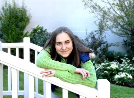 hooded vest: Attractive female teen relaxes on a white wooden fence in garden.  She is wearing a light green sweater and hooded blue vest.  She grins happily. Stock Photo