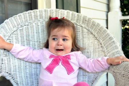 reacting: Toddler reacts with real fear when a spider approaches her white wicker chair.