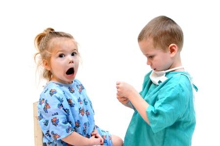 Dos niños juegan médico. La niña abre la boca y dice: aaah! Pero es casi una expresión de pánico como el doctor niño ajusta su instrumento. Uno está vestido con bata de hospital y el otro un lavado con mascarilla facial. Foto de archivo - 15044691