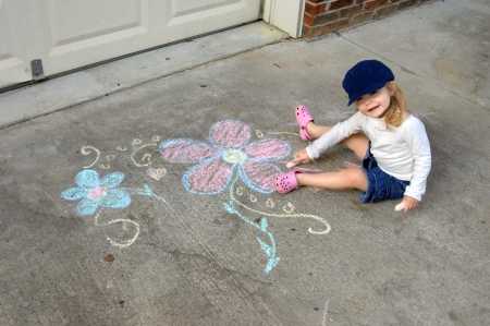 Beginning artist creates on the driveway of her home.  She is wearing a denim skirt and cap and drawing with sidewalk chalk. Stock fotó - 15044756