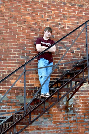 Young man leans against a brick building while ascending a black metal fire escape in a town in Alabama   He is wearing jeans and a torn tee shirt
