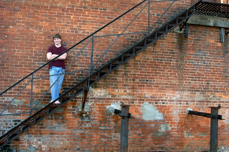 Brick wall and fire escape serves as a resting place for young teen   He is wearing jeans with hole at knee and a torn burgundy tee shirt