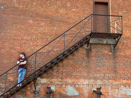 Black iron fire escape serves as resting place for young teen as he leans back against an aging brick wall  photo