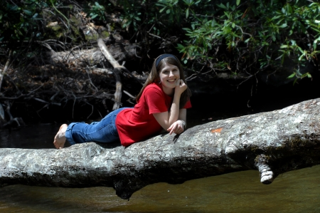 Young woman lays on tree trunk that has fallen across a quiet stream.  She is smiling and happy.  Barefooted and wearing jeans. photo