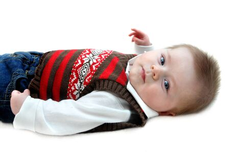 contented: Contented baby boy lies on all white carpeted floor.  Image is isolated and baby is looking with eyes wide open.  He is wearing jeans and sweater vest.