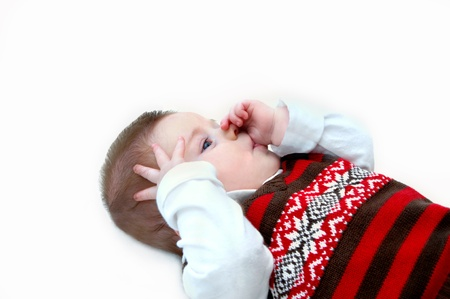 absorbed: Tiny baby lays on all white floor and sucks his thumb.  He is totally absorbed in himself.  His vest is brown and red knit and covers a white long-sleeved turtle neck shirt. Stock Photo