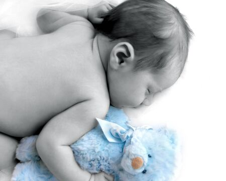 Newborn infant cuddles his blue teddy and sleeps in a dreamland of white.  Blank space for personalization. Stock Photo - 15044672