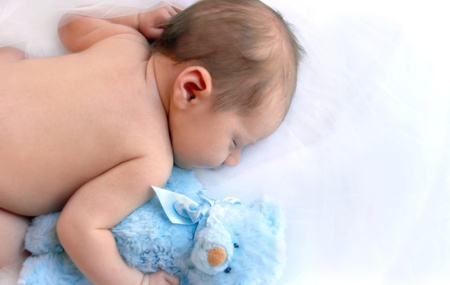 Newborn infant cuddles his blue teddy and sleeps in a dreamland of white.  Blank space for personalization. Stock Photo - 15044687