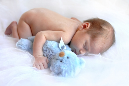 Tiny newborn booy hugs a blue teddy bear and slumbers away.  Soft white netting cushions his nap.