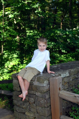 Small guy relaxes on a stone wall.  He is leaning back and feeling quite confident.  He has on khaki shorts and a white shirt with a great big smile.