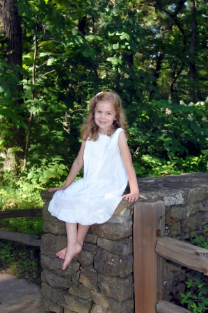 little girl barefoot: Young lady sits on a rustic stone wall in the Birmingham Botanical Garden in Birmingham, Alabama.  She is wearing a white eyelet dress and smiling, happily. Stock Photo