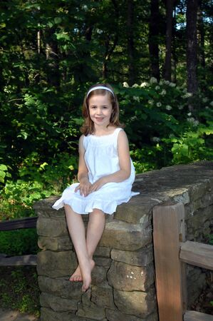 Beautiful young girl sits on a stone wall surrounded by the Birmingham Botanical Garden in Birmingham, Alabama.  She is wearing a white dress and pretty smile. photo