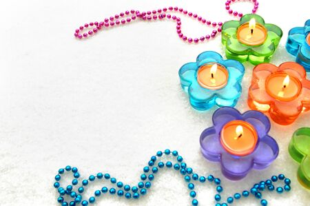 Candles are burning in colorful daisy shaped candles holders.  Colorful beads lay on white carpet. Stok Fotoğraf