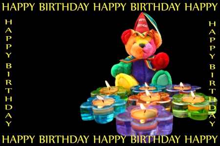 Happy Birthday teddy bear sits in front of flower shaped candles.  Candles are burning and in fun colors of blue, purple, green and orange. photo