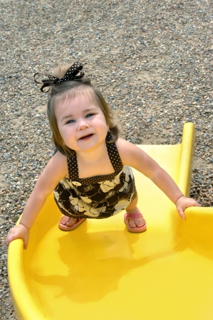 Baby crawls up the slide instead of sliding down the slide.  She is struggling upward but pauses to look up and smile.  Brown print sundress and sandals. photo
