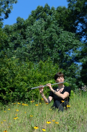 Flute player, dressed in black, sits on a grassy hillside with colorful wildflowers.  Forest, trees and blue skies surround the back.