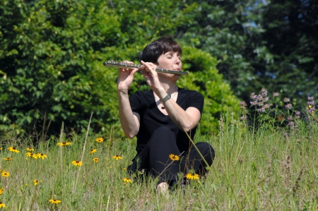 enraptured: Female flute player is immersed in her music as she sits on a hillside amoung the wildflowers.  She is wearing black and her eyes are closed.
