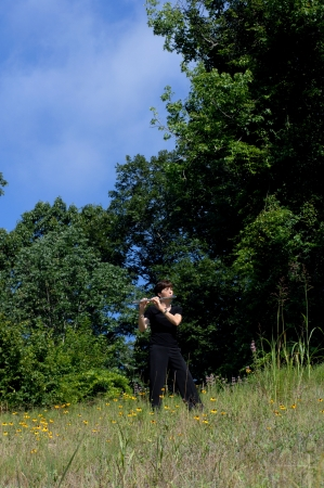 immersed: Female flute player stands on a grassy hillside and plays to the breeze.  Wildflowers in purple and yellow surround her.  She is wearing black and her eyes are closed. Stock Photo