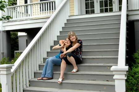 Mom and daughter sit on porch steps making faces and smiling.  Wooden steps have peeling grey paint. photo