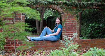 Young woman occupies an old brick arch in a shady garden.  She is wearing jeans and smiling happily.  Brick wall runs length of photo. photo