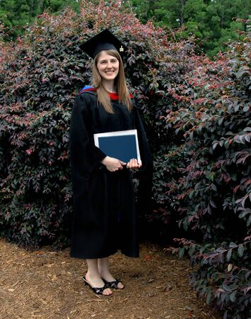 masters degree: Female graduate with masters degree poses with black gown and hat. She is holding a degree with blue cover.  Stock Photo