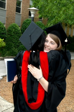 Female graduate hugs friend after graduation  Both are in black cap and gowns  One is holding degree
