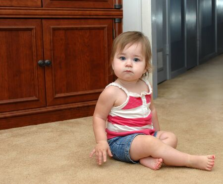 u�as pintadas: Beb� hace una pausa mientras se enfrenta a sus miedos de la oscuridad del pasillo en sus pantalones cortos de mezclilla de origen y la parte superior de verano con u�as de los pies desnudos pintados de color rosa Foto de archivo