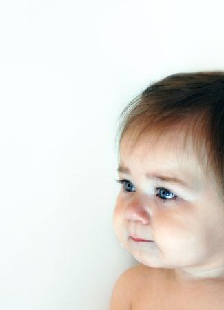 teary: Baby sits in corner with tears running down her cheeks   Dark hair and deep blue eyes   Tears brim her eyes