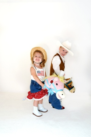 Brother and sister saddle up for a little fun   Both are dressed in western wear and astride stick ponies