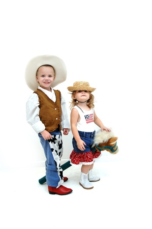 Brother and sister share a horse in their adventures   Both are dressed in western wear complete with boots and hats   Both are sharing a stick horse  photo