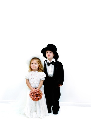 Small girl and boy dress in wedding gown and tuxedo   She is wearing a hat and veil and he a top hat   They are standing in a all white room
