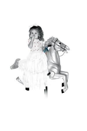 Little girl sits on a carousel horse wearing a long white dress.  She is sucking her thumb and dreaming in her own little world.  Hairbow and curls. photo