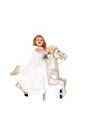 steed: Small child rides a carousel horse in a white dress and white hairbow.  She is thrilled and excited as she imagines her wild ride through the skies. Stock Photo