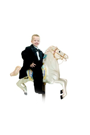 imagines: Small child rides a carousel horse in a in a black tuxedo.  He is thrilled and excited as he imagines his wild ride through the skies.
