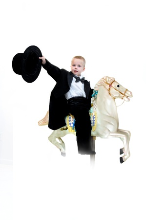 Young boy rides his stallion into a new adventure.  He is wearing a black tuxedo and waving a top hat.  His ride is a carousel horse. photo