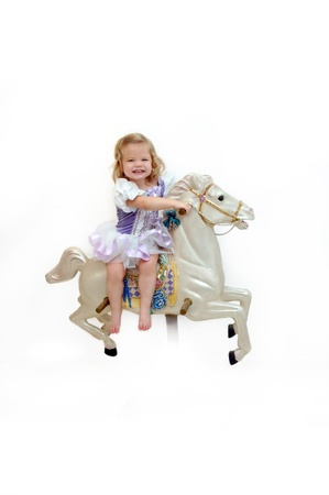 Little girl giggles with delight as she rides a carousel horse.  She is dressed in a ballerina costume and is barefoot.  Blond hair and a big smile. photo