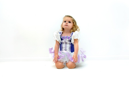 be dressed in: Young child dressed in ballerina costume, kneels on the floor of an all white room.  She seems to be listening or dreaming of stardom.