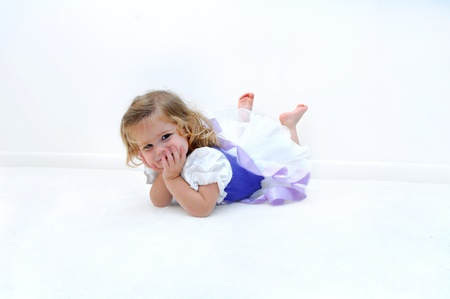 A tired little ballerina lays on the floor in an all white room.  She is dressed in a ballerina costume of lilac and purple.  Child is grinning and resting her head in her hands.