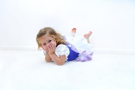 sprawled: Una peque�a bailarina cansada se acuesta en el suelo en un cuarto blanco. Ella est� vestida con un traje de bailarina de lila y morado. El ni�o est� sonriendo y descansando su cabeza en sus manos.