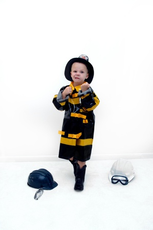 Small boy puts his fists up to help him fight against fire.  He is wearing a firemans costume and hat.  Two helmets and a pair of goggles lay on the carpet in an all white room. photo