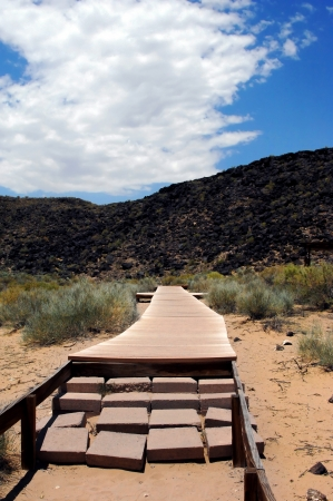Rustic wooden walkway leads to the petroglyphs at Petroglyph National Monument in Albuquerque, New Mexico   Black basalt rocks line the mesa above
