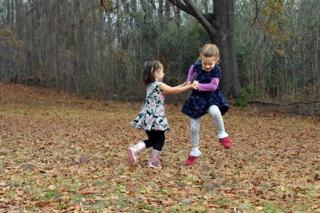 Two friends dance for joy in the Autumn leaves in Arkansas   They are holding hands and jumping high and running in circles  photo